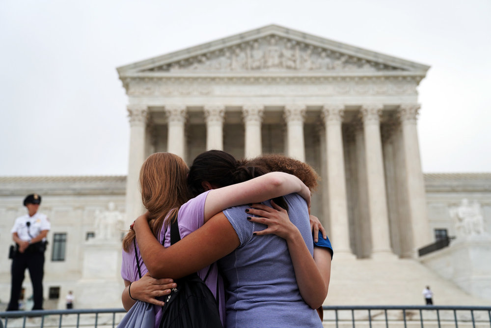 Demonstrators hug outside the Supreme Court at the end of a protest against Justice Brett Kavanaugh on the first day that Justice Kavanaugh sat on the bench and heard oral arguments, in Washington, DC on October 9, 2018.