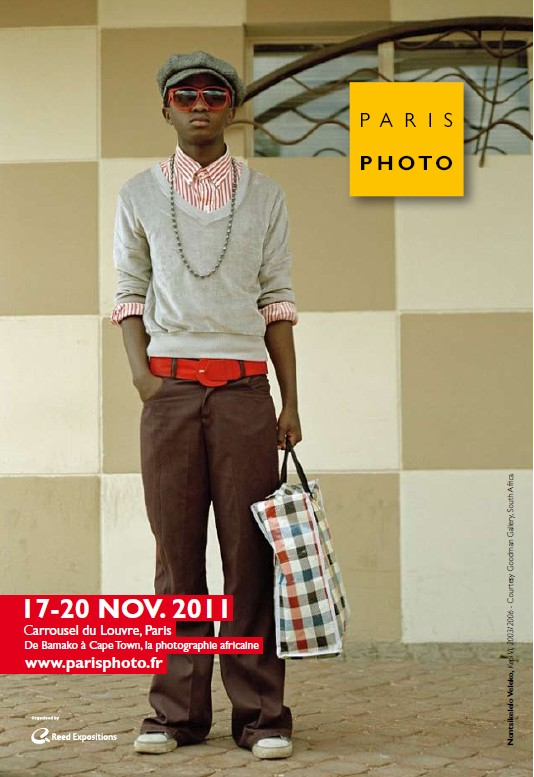 Poster for Paris Photo 15th edition of boy standing with sunglasses and red belt. Commerce and Culture are very excited that Paris Photo is set to highlight sub-Saharan African photography from Bamako to Cape Town in its 15th edition.