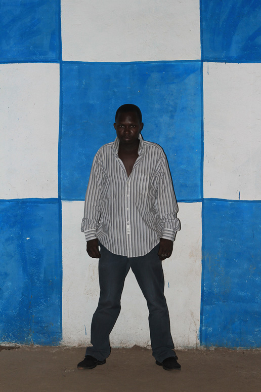 Photo of man standing in front of a wall with blue and white checks, is taken by Aboubacar Traore for the Bamako Nightlife.