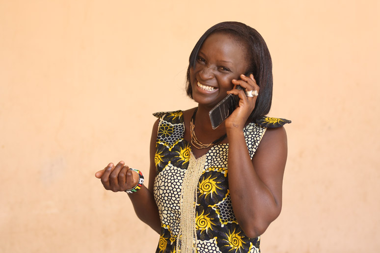 Photo of woman smiling while on the phone, is taken by Seydou Camara in 2010, who is part of Commerce and Culture's stock program.