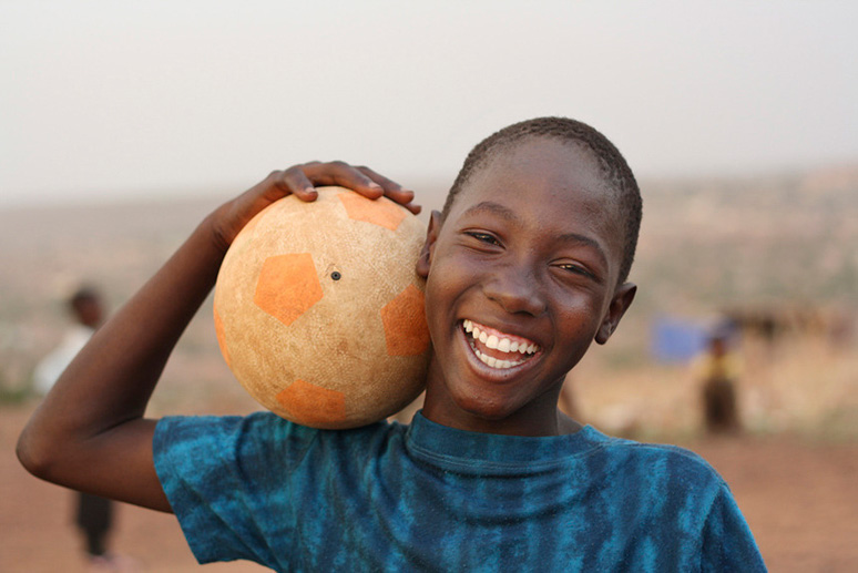 Photo of boy smiling while he is holding a football, is taken by Aboubacar Traore, who is part of Commerce and Culture's stock program.