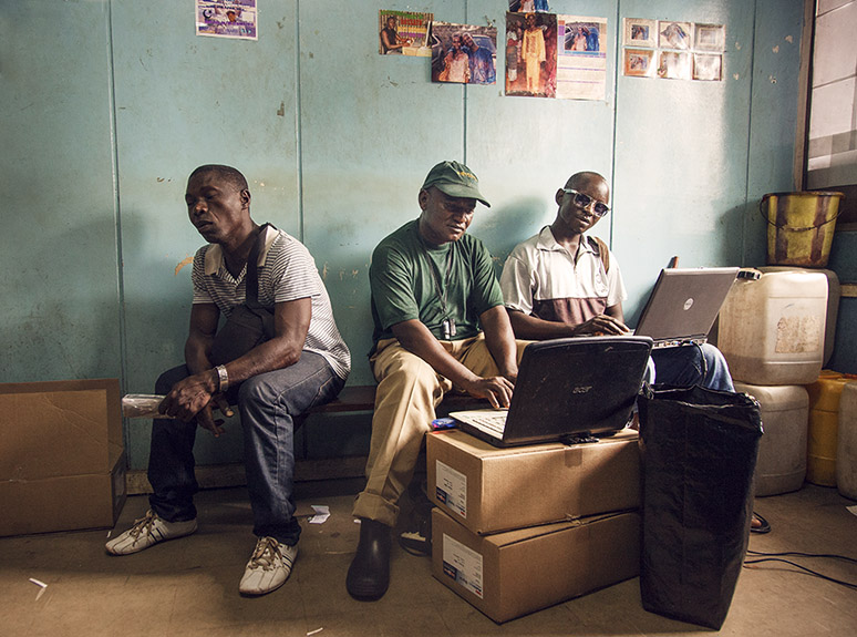 Preparing images for printing inside Lab, surrounded by lab supplies in Freetown, Sierra Leone.