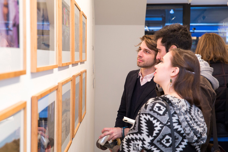 commerce-and-culture-afghan-tales-opening-night-munch-gallery-three-people-looking-photo-wall.jpg