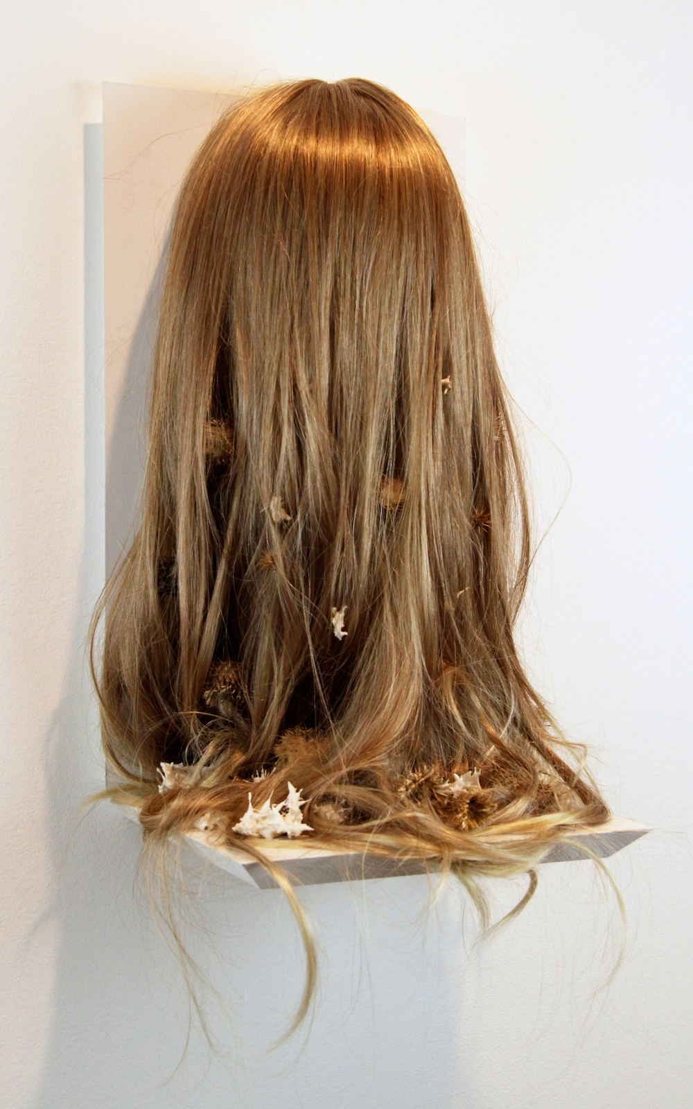 "lonelily loomed into bone.     wig, thistles, porcelain. 17 1/2 x 13 x 12"". 2011"