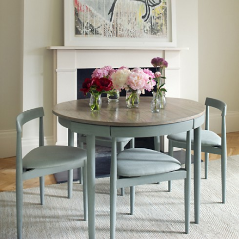With handy pull out chairs, this round table from Chelsea Textiles adds  some mid-century modern and space saving style.