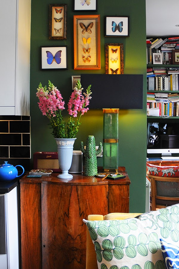 A dark green wall is offset by a collection of framed butterflies in his London apartment