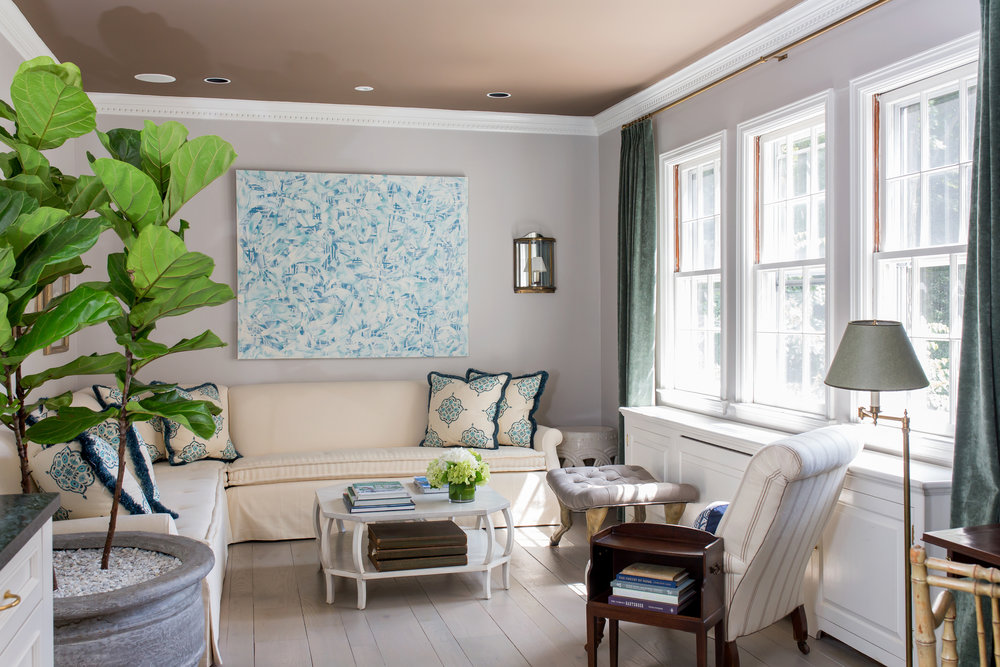 Floret, a painting in blue and white hangs above the sectional sofa and complements the throw pillows used there