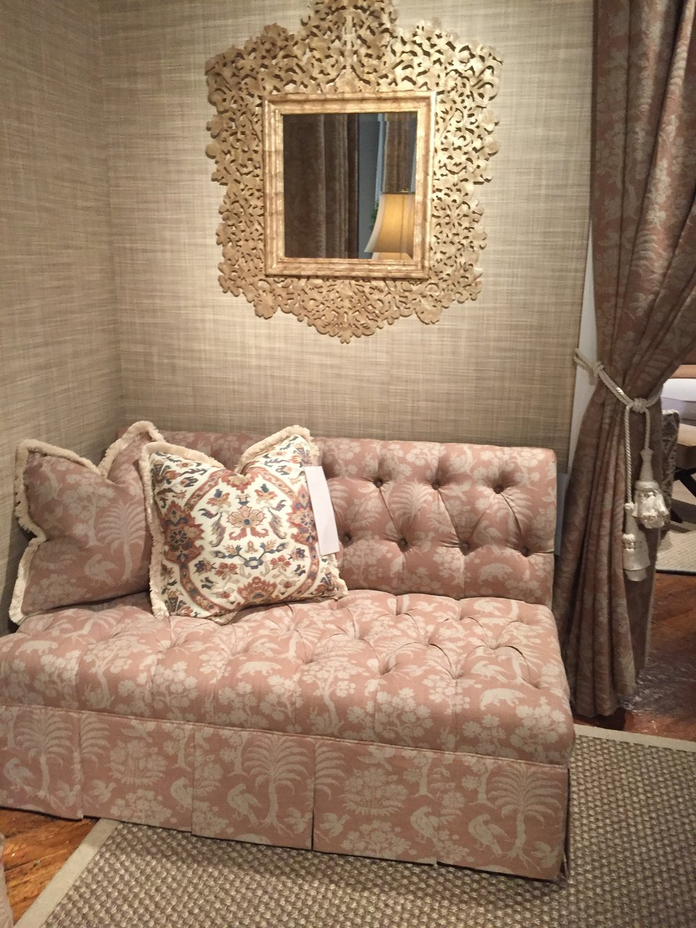 A Dusty Pink And Creme Palm Tree Print Covers An Upholstered Corner Settee  With Tufting And A Tailored Skirt