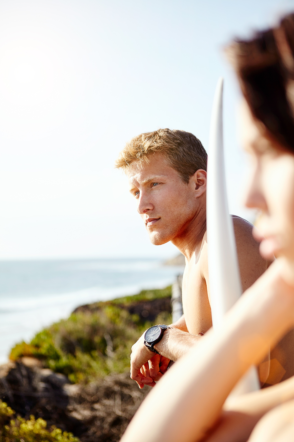 lifestyle blonde male surfer looking out at ocean waves.jpg