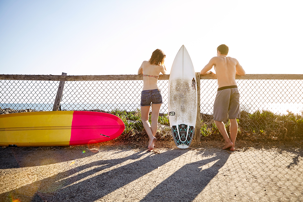 lifestyle girl and guy lookint at ocean waves at fence with surfboards.jpg
