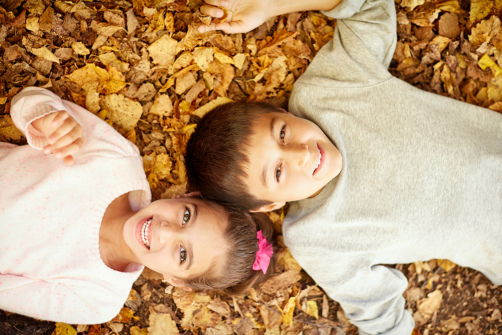 Boy and girl lying in fall leaves.jpg