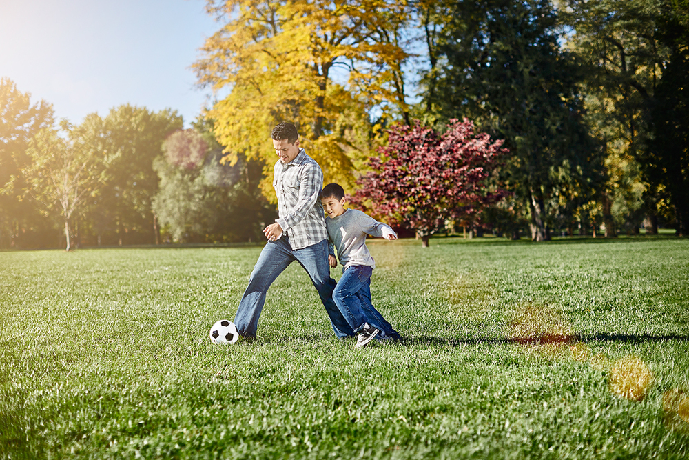 Father and son playing soccer in a field.jpg