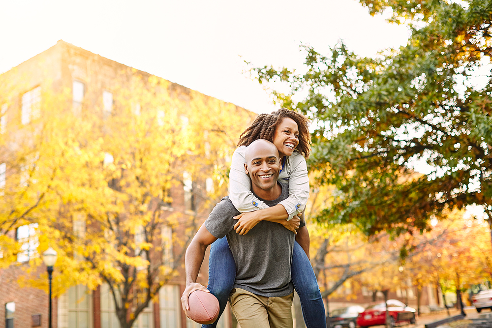 girl and guy piggyback playing football.jpg