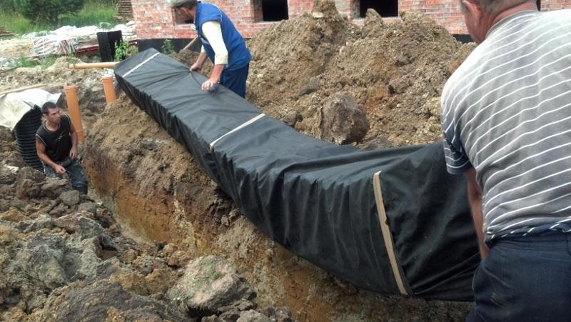 Рабочие укладывают трубу в землю