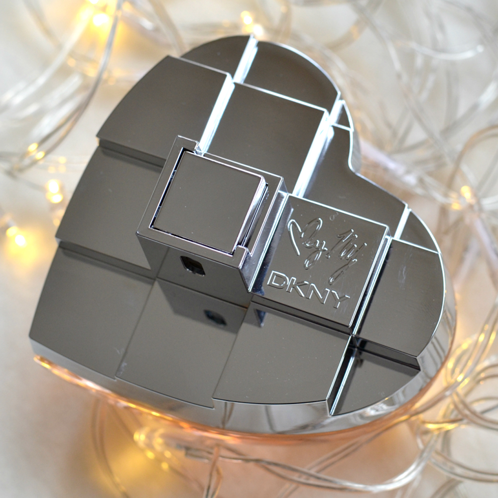 The DKNY MYNY is shaped like a heart and made of glass and metal.