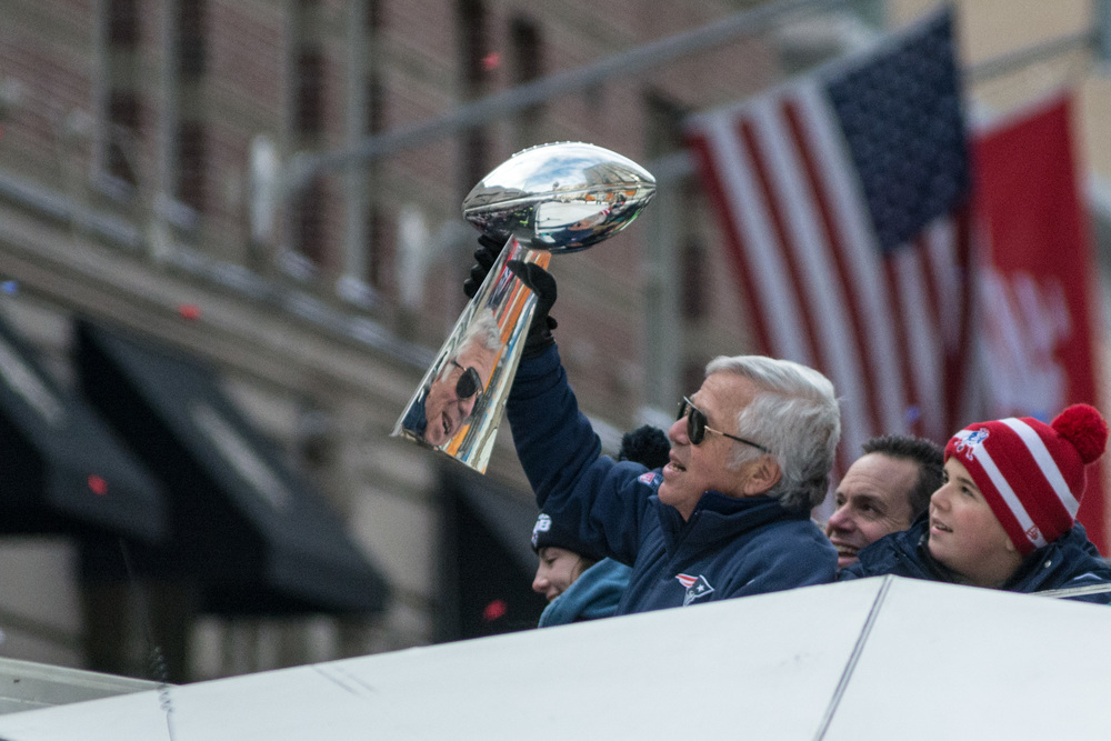 Patriots owner Bob Kraft holding one of four  Vince Lombardi Trophies