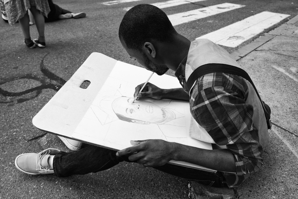 One of the marchers drawing a portrait of Mike Brown