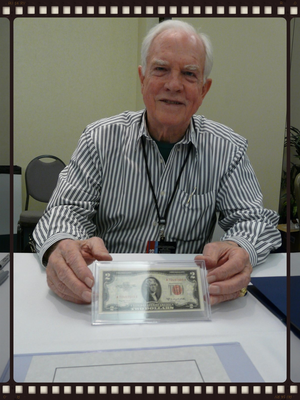 Apollo 15 Commander and moonwalker David Scott holding the flown $2 bill at the Astronaut Scholarship Foundation gathering in November of 2008.