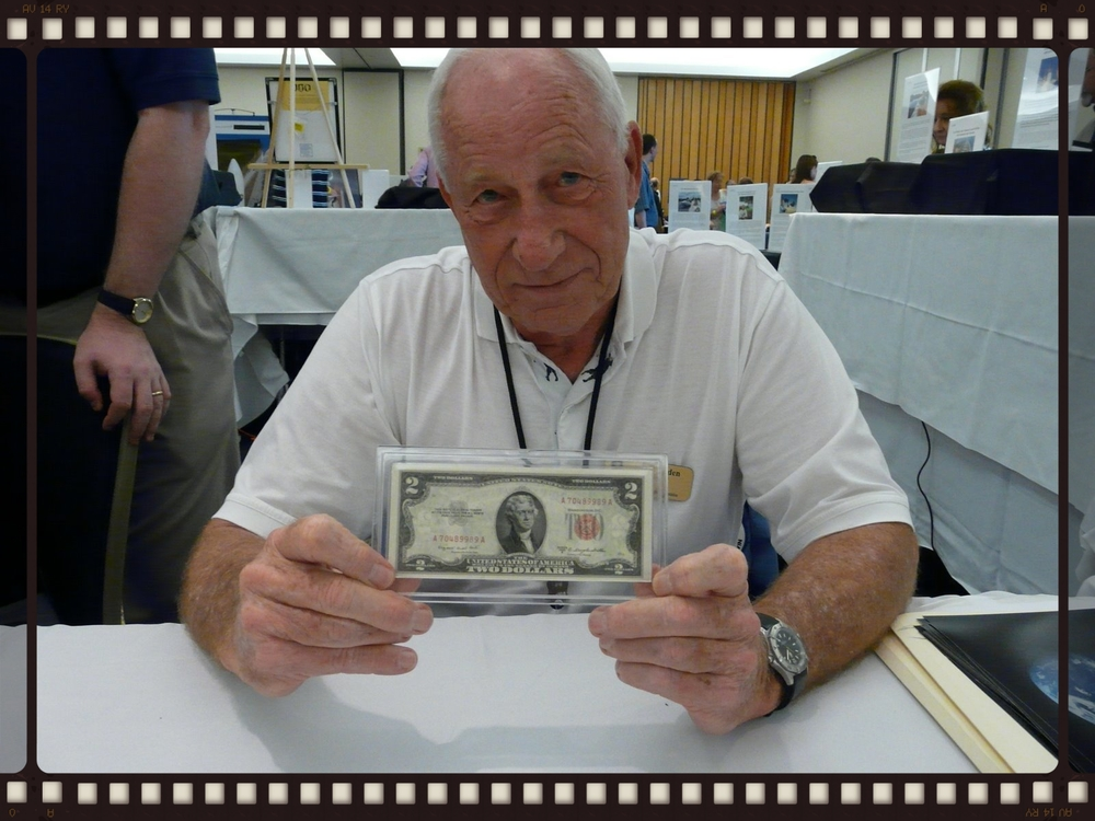 Command module pilot Al Worden, who flew solo with this bill in lunar orbit will Dave Scott and Jim Irwin walked on the surface of the moon, holds the flown $2 bill at the same ASF event in 2008.