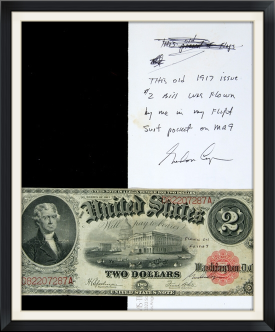 The flown bill along side the envelope in which it was housed, with Gordon Cooper's flight certification on the bill and the envelope. According to the envelope and the note, written in Cooper's own hand, this particular bill was folded and stored in his flight suit pocket for the flight.
