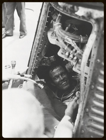Gordon Cooper as first seen when his Mercury Atlas-9 capsule hatch is opened aboard the recovery ship after his flight. Tucked safely in one of his suit pockets, the flown $2 bill.