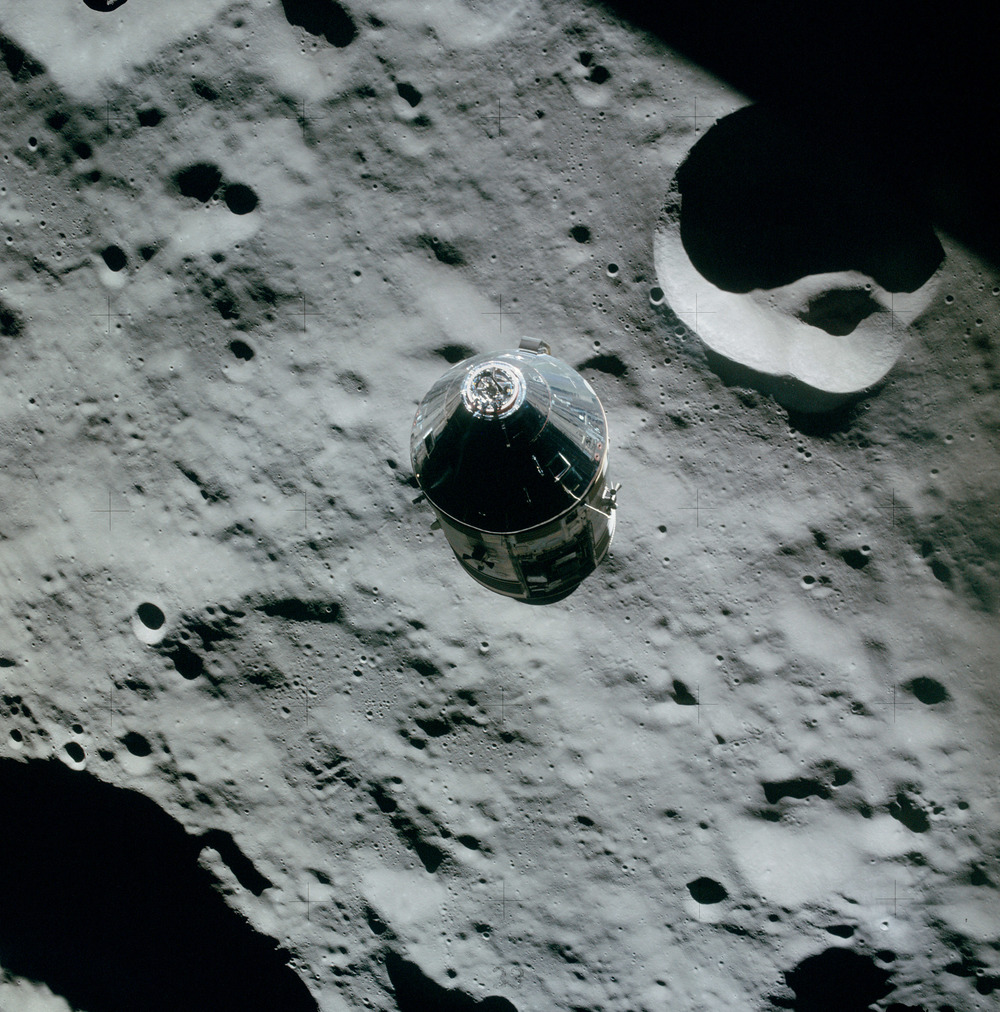 "Apollo 16 Command Module ""Casper"" during one of its 64 orbits of the moon, as photographed from Apollo 16 lunar module ""Orion."" Aboard Casper, tucked carefully among the crew's PPKs, is this series 1963, red seal $2 bill, S/N A02317535A,"