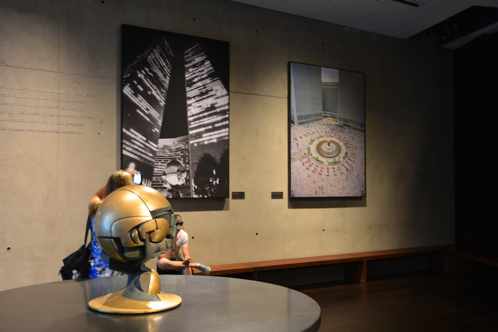 Concourse Lobby of the Museum: A model of The Sphere and pictures of it (background) in its original setting next to the Twin Towers. It actually spun in the middle of the fountain and is now located in Battery Park with the damage of the fallen Twin Towers readily evident on the top and sides of the structure.