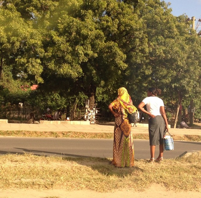 Local women crossing the street in down town Dar-Es- Salaam the woman on the right is creating a hijab out of kanga material and the woman on the right is in western clothing.