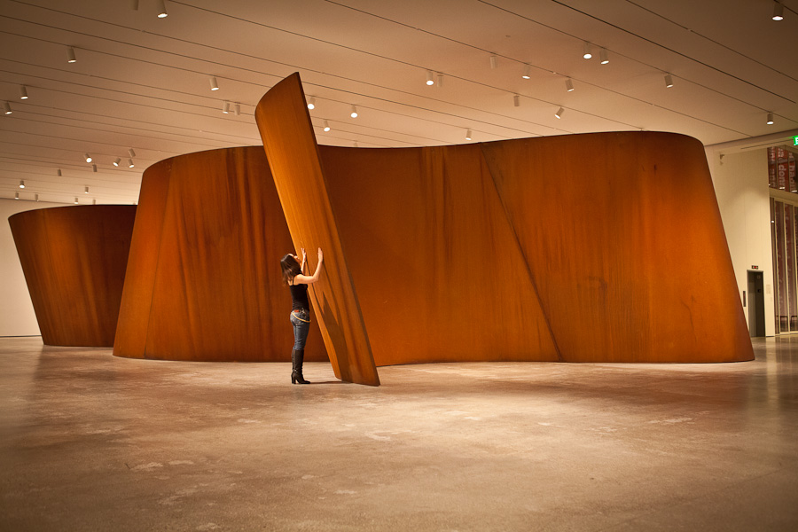 Richard Serra, Band (2006) 200' x 13' (200 tons)Corten Steel Plate   The artist frequently works at a huge, overwhelming scale, forcing viewers to consider the way their bodies relate to his sculptures. They can often walk around, inside, and through the work, feeling its curves and passages mold both their physical space and their visual experience of that space.