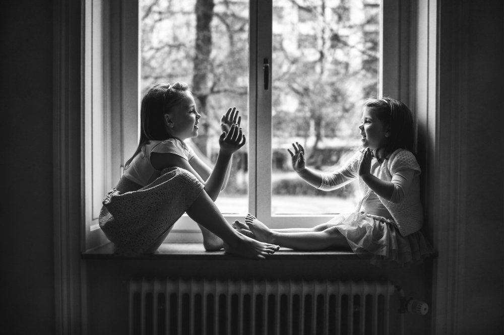 Black-and-white-image-of-sisters-playing-in-window-by-Stockholm-barnfotograf-Sandra-Jolly.jpg