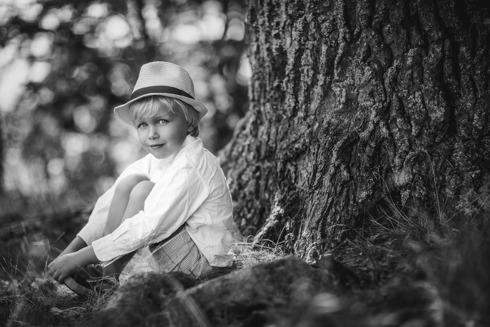 A-black-and-white-portrait-of-a-little-boy-in-a-straw-hat-by-Sandra-Jolly-familjefotograf.jpg