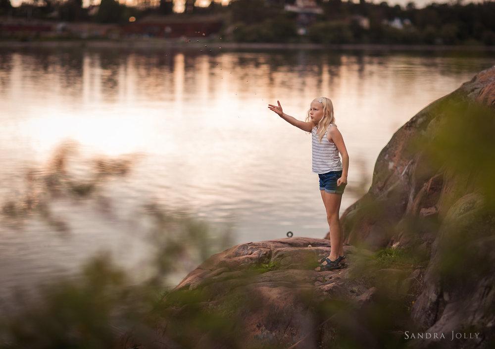 girl-throwing-stones-at-Edsviken-by-Sollentuna-barnfotograf-Sandra-Jolly.jpg
