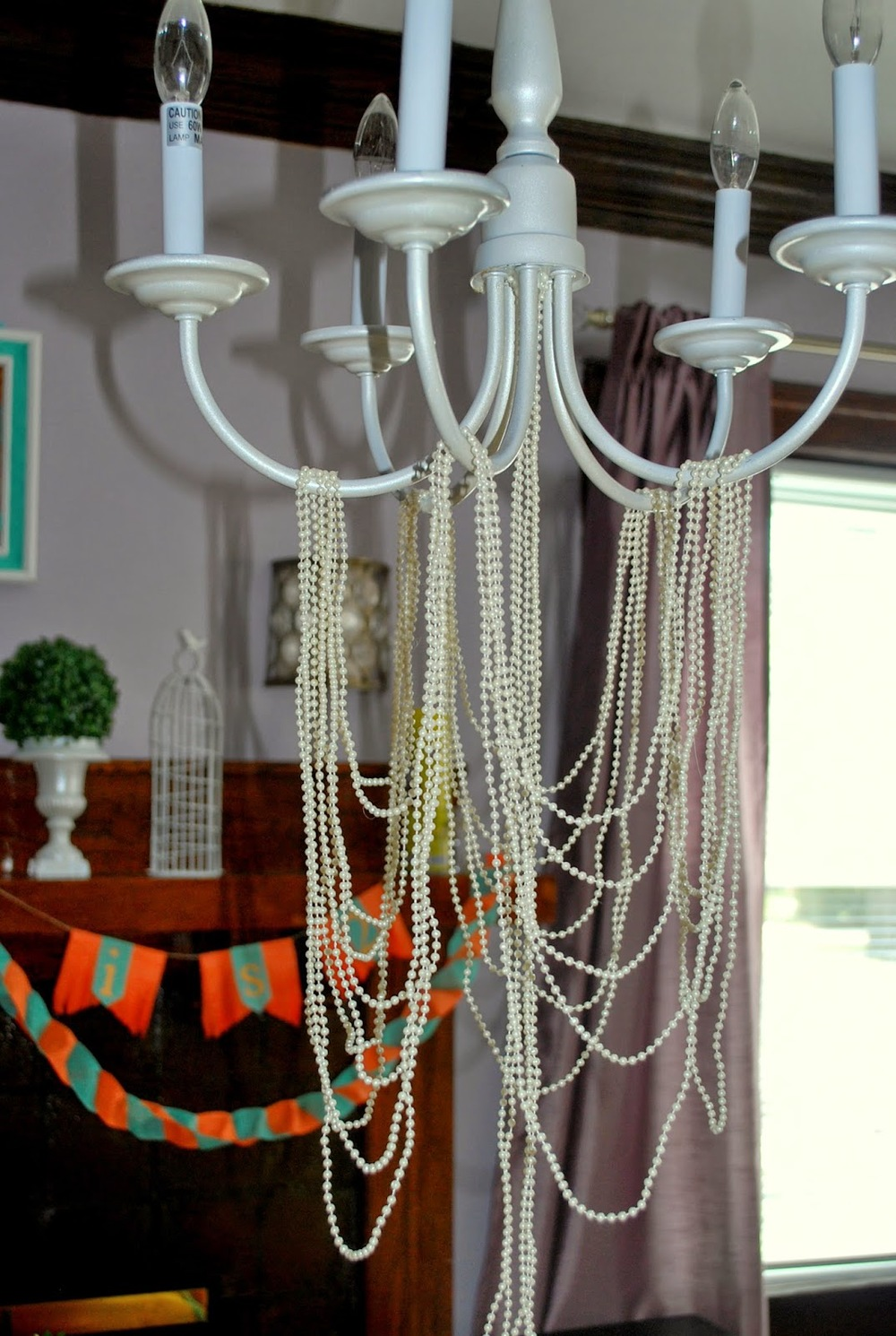 Natasha was searching for many weeks for the perfect chandelier to use as an overhang for the children's table. She discovered the perfect one on Craigslist. She spray painted and decorated it with pearl strands. Super chic!