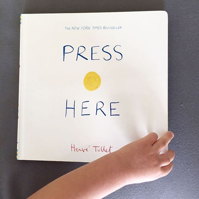 """One of our favorite books is on the blog today – """"Press Here"""" by @hervetullet is a genius book filled with colors, entertainment and yet simplicity. """"Press here and turn the page"""" – """"Great! Now press the yellow dot again."""" – """"Perfect. Rub the dot on the left.. Gently."""" … Not just Mila has fun with it. Link in profile."""