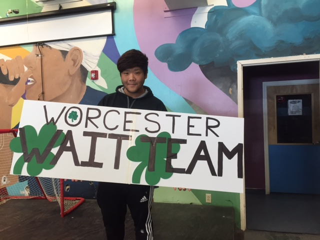 Team member Paul Takahashi displays his sign work before the parade.