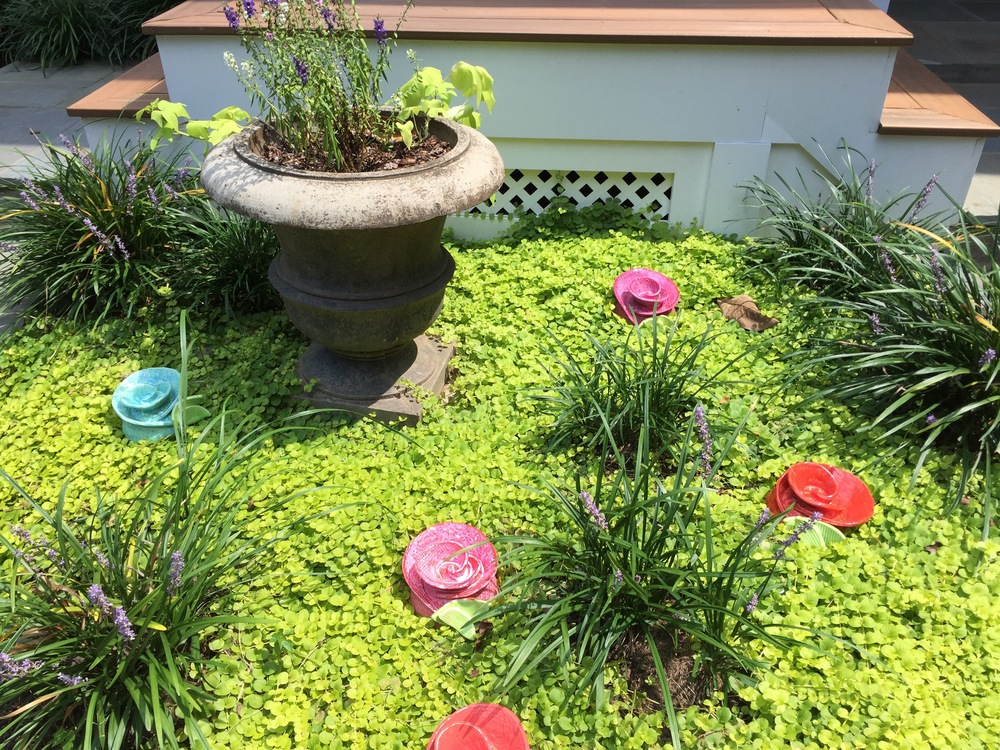These toad houses bring a pop of color to this beautiful garden area!