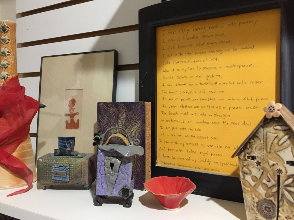 One of the shelves in my studio houses a collection of pottery I've purchased or were gifted to me. The poem was written by a young friend exploring his clay skills in high school. The red scarf was given to my son by the Dalai Lama. I bought the paper cut-out art (on the left) when I was in college.  This assemblage both inspires and makes me happy.