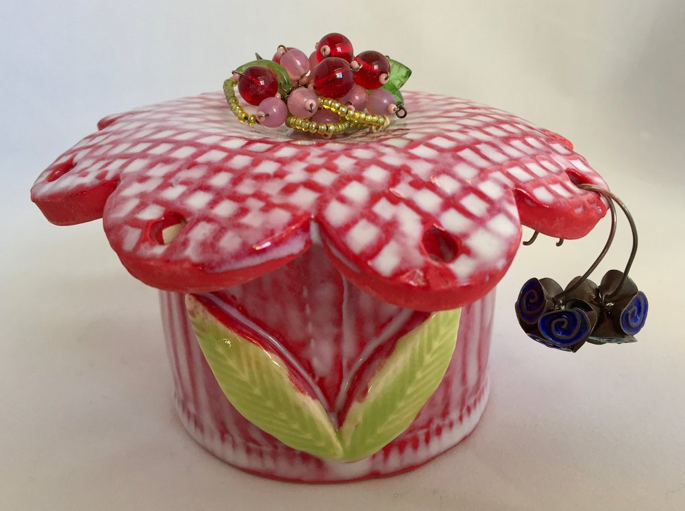 I like to mix materials in my creations. This little jewelry jar uses bits of recycled earrings and broaches as the center of each lid. Another form of a second act?!?