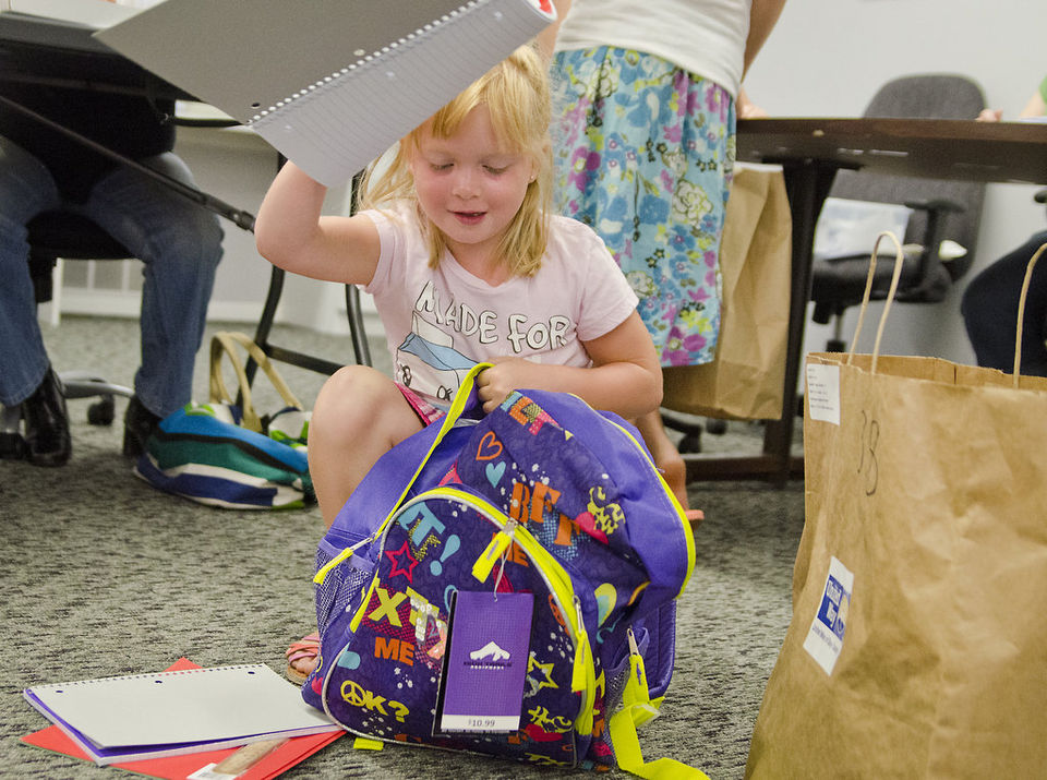 A local girl RECEIVES a new backpack for the 2013 school year. (Photo courtesy MLIVE)
