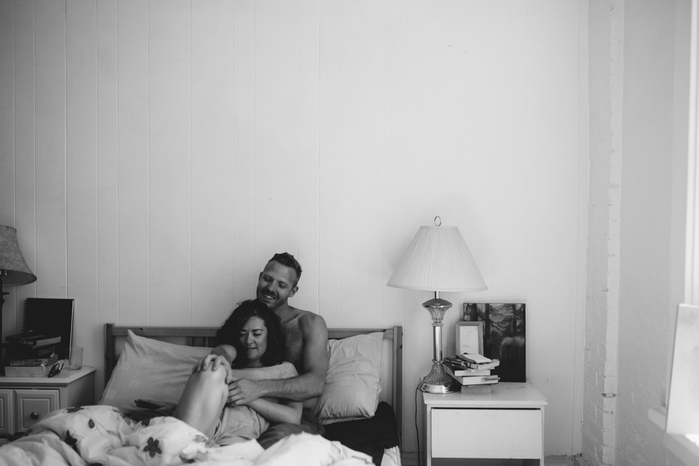Couple laying in bed intimate at-home engagement session in Victoria BC