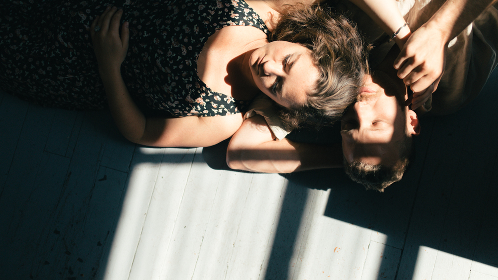 Couple lying in sunbeam intimate at-home engagement session in Victoria BC