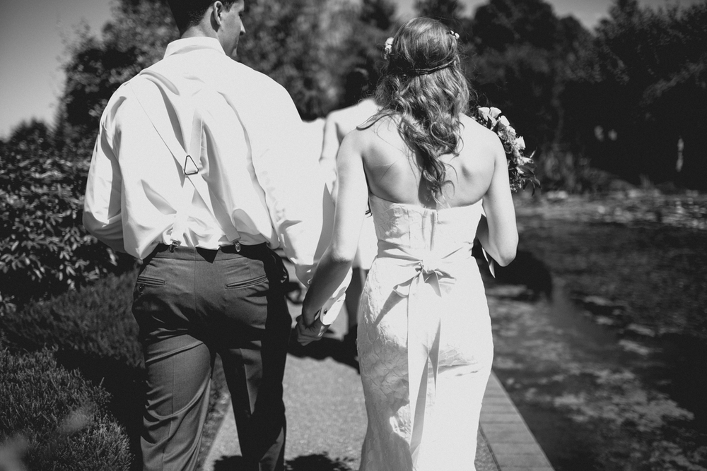 Newly wed couple Bride and Groom walking while holding hands King Francis Park Forest Wedding Vancouver Island
