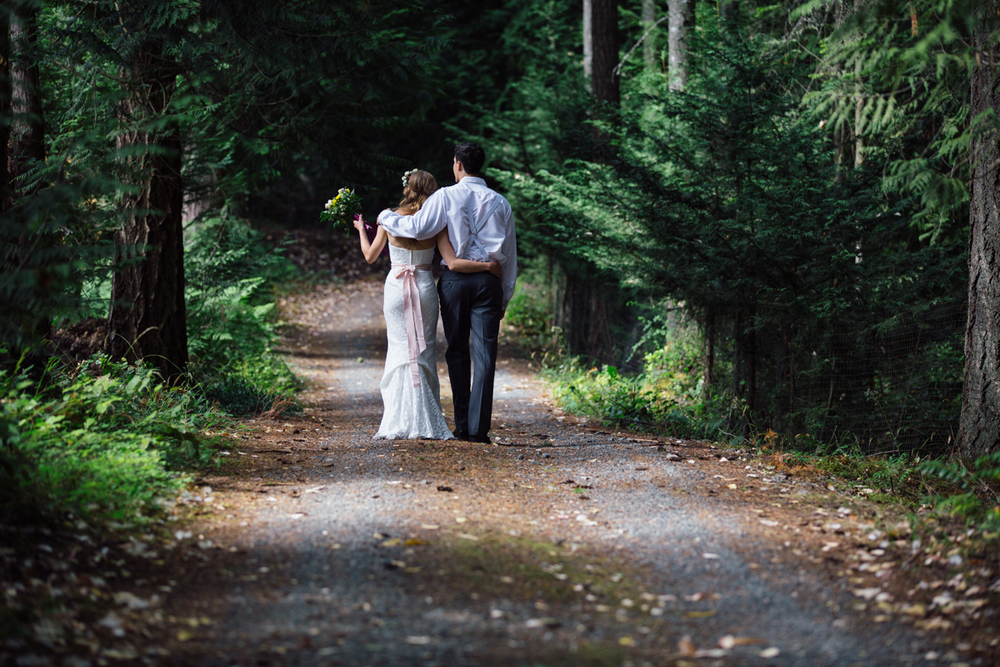 The Bride and The Grooms walking in forest pathway The Guild wedding reception King Francis Park Forest Wedding Ceremony Vancouver Island