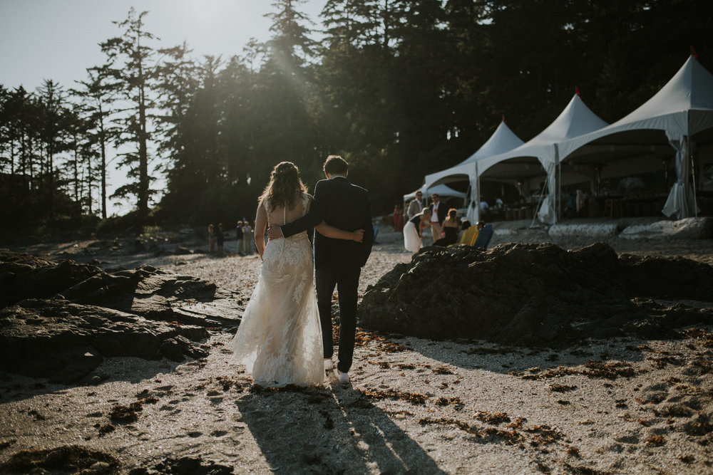 married couple walking to reception on seashell beach wedding tofino
