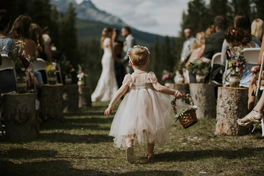 cute flower girl walks down isle mt norquay wedding banff