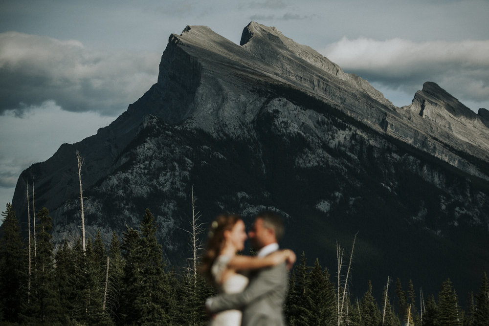 couple embraces against banff mountains wedding