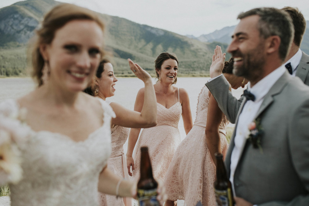 bridal party celebrates at lake in banff