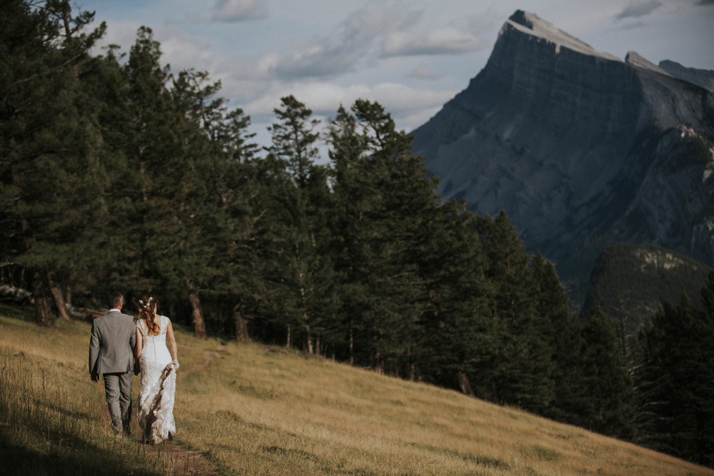 married couple walks along mountain meadow mt norquay