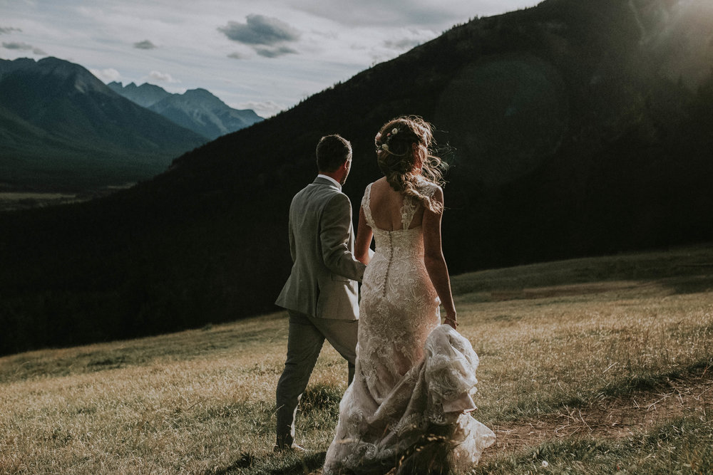 couple walks on mt norquay after wedding banff