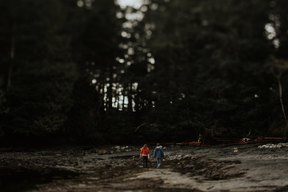 Couple walking towards the trees Beach Engagement Botanical Beach Juan de Fuca